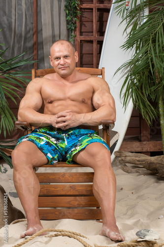 Muscular man on beach with surfboard near house