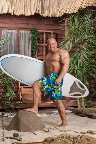 Muscular man on beach with a surfboard in hand