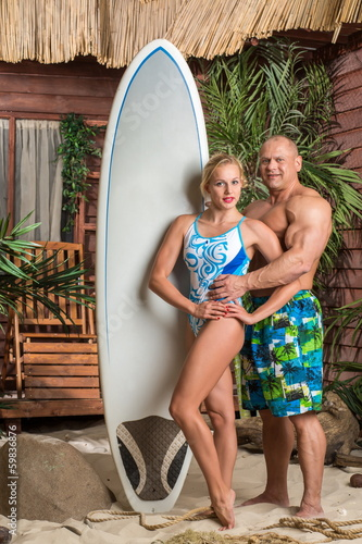 Muscular man and girl with surfboard on beach