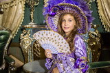 girl in old-fashione dress  with fan in beautiful room
