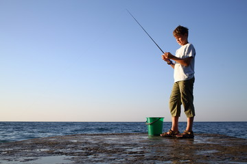 boy with a fishing rod and bucket fishing in sea with horizon