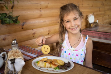 Little smiling girl sitting in a cafe at the table with food