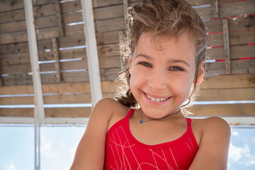 Smiling girl in red swimsuit under wooden roof
