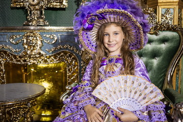 The girl in old-fashione dress  with fan in beautiful room