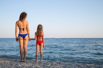 Mother and daughter in swimsuit standing on beach