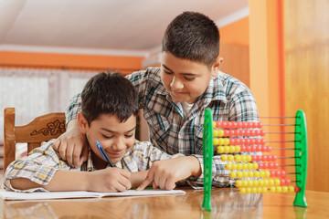 Two little boys write homework