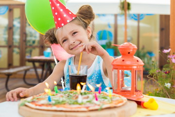 Little girl in celebratory cap in cafe with a pizza