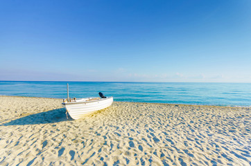 Boat on empty sea beach and horizon at sunrise