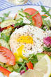 Vegetable salad with poached egg on a plate, vertical, closeup