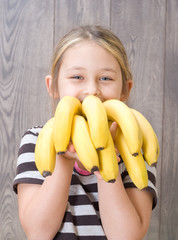 child holding a bunch of bananas
