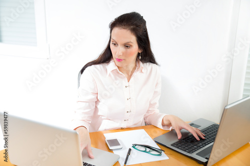 Portrait of a businesswoman with lots of work at office desk