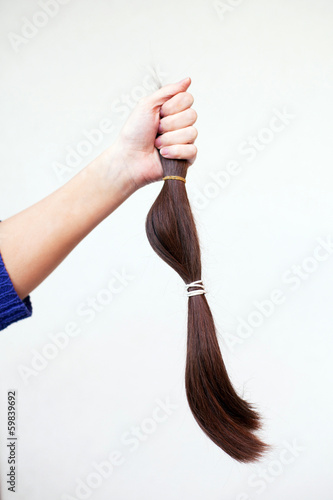 hand holding cut off ponytail of hair