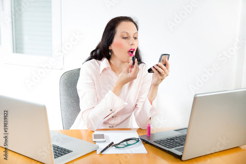 business woman  using lipstick in the office