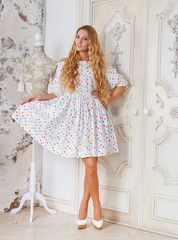 Portrait of the beautiful blond girl in polka dots dress