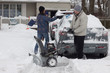 Father and sons clearing snow after storm