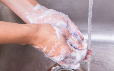 Female washing hands with soap at the kitchen sink