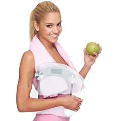 Attractive young woman with apple, scales and towel around the n
