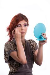 Young woman applying make up