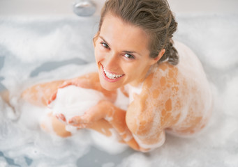 Smiling young woman playing with foam in bathtub