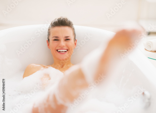 Smiling young woman having fun time in bathtub