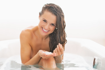 Happy young woman applying hair mask in bathtub