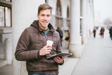 Young man drinking coffee on the street while using tablet compu