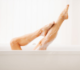 Closeup on legs of young woman in bathtub