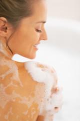 Happy young woman washing in bathtub