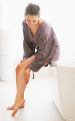Young woman checking leg skin softness in bathroom