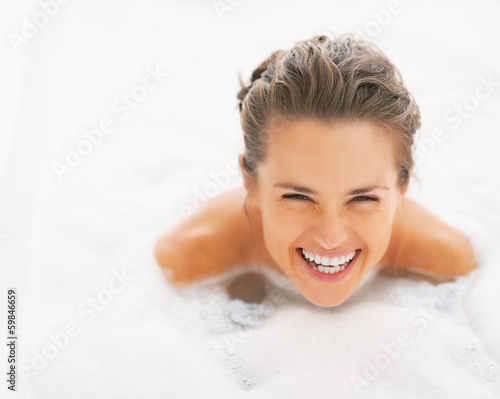 Portrait of young woman among foam in bathtub
