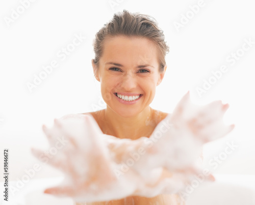 Smiling young woman showing hands in foam