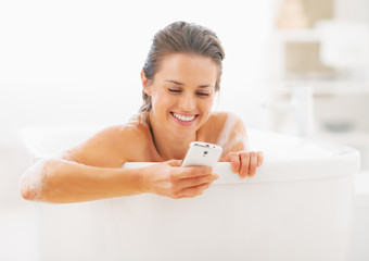 Smiling young woman writing sms in bathtub