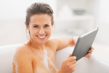 Happy young woman using tablet pc in bathtub