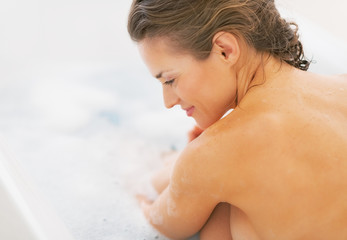Relaxed young woman sitting in bathtub. rear view