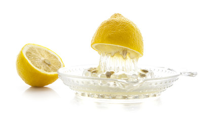 Glass citrus squeezer with lemons and juice on a white backgroun