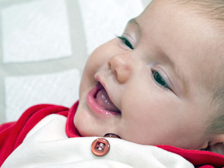 newborn baby smiling on bed