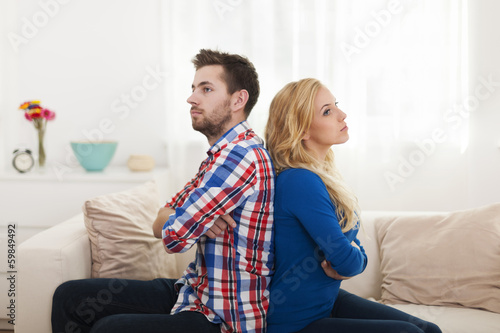 Angry young couple sitting back to back at home