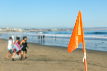 Lifeguard flag,beach shoreline for water safety,people.