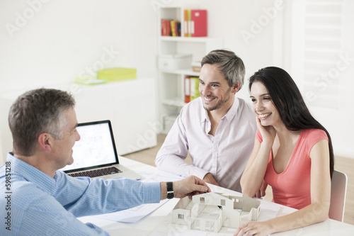 real estate agent showing a construction project to a couple