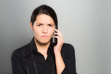 Verwirrte Frau telefoniert mit ihrem Mobiltelefon