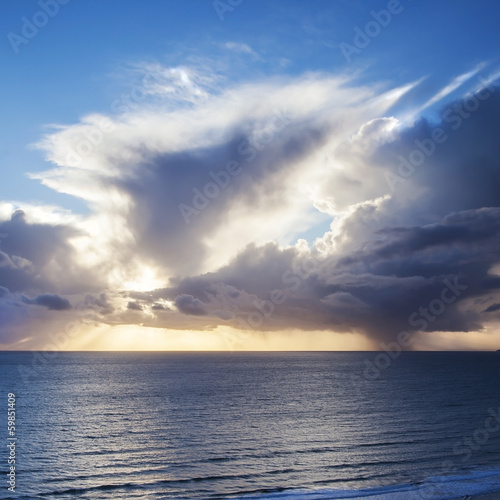 Amazing seascape with sunset rays and clouds over sea