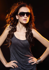 young woman in sunglasses wearing black dress