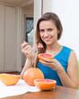 girl eating grapefruit at home
