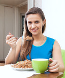 Smiling woman eats buckwheat