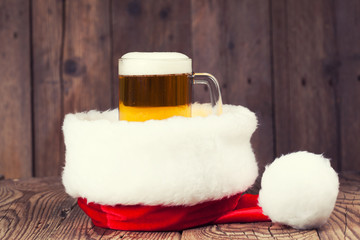 mug of beer with Santa's hat on wooden background