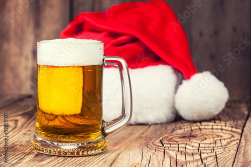 Plexiglas Bier mug of beer with Santa's hat on wooden background