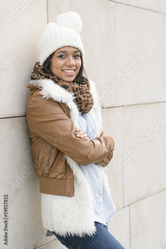 Portrait of smiling woman with bonnet on wall background.