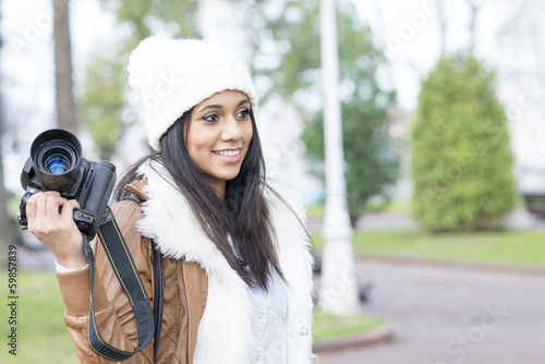 Portrait of smiling girl with professional camera, outdoor.
