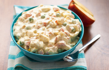Vegetable salad with mayonnaise sauce with an apple on the table