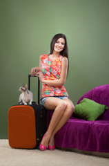 Smiling pretty girl going on vacation with her cat